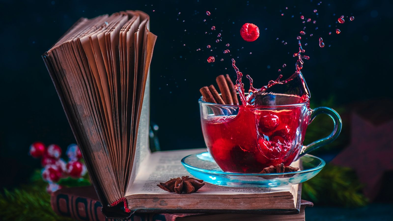 Red berry tea on a stack of books with a dynamic splash. Winter hot drink on a dark background with copy space